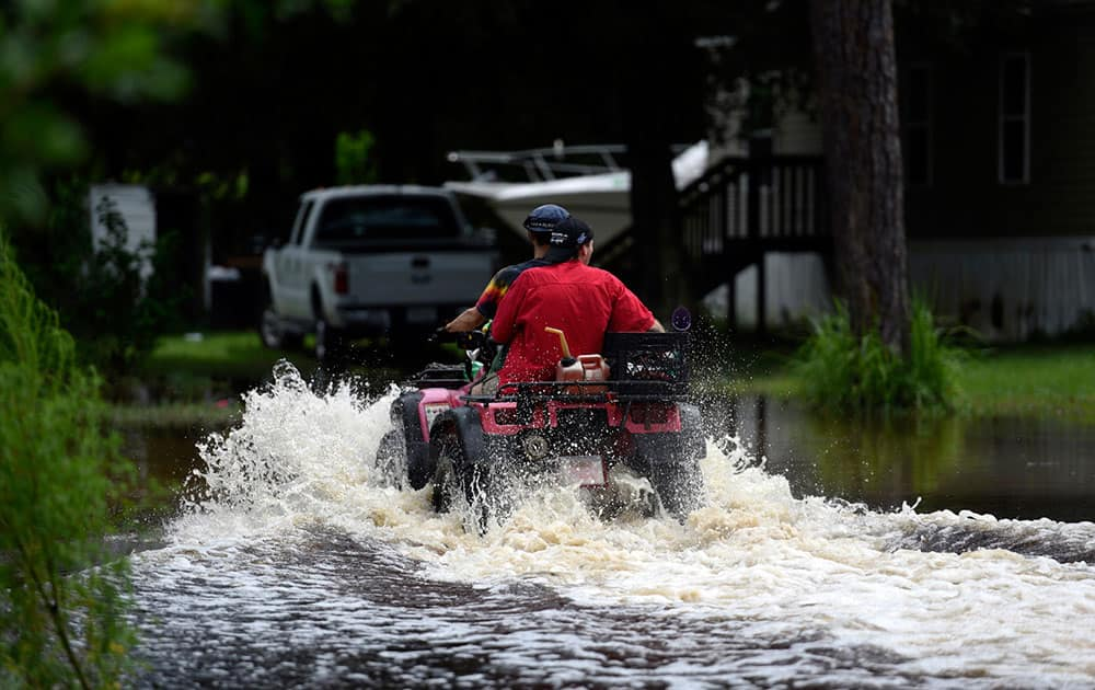 People ride on an all-terrain vehicle near the intersection of Ringgold Avenue and Elfers Parkway in Elfers, Fla.