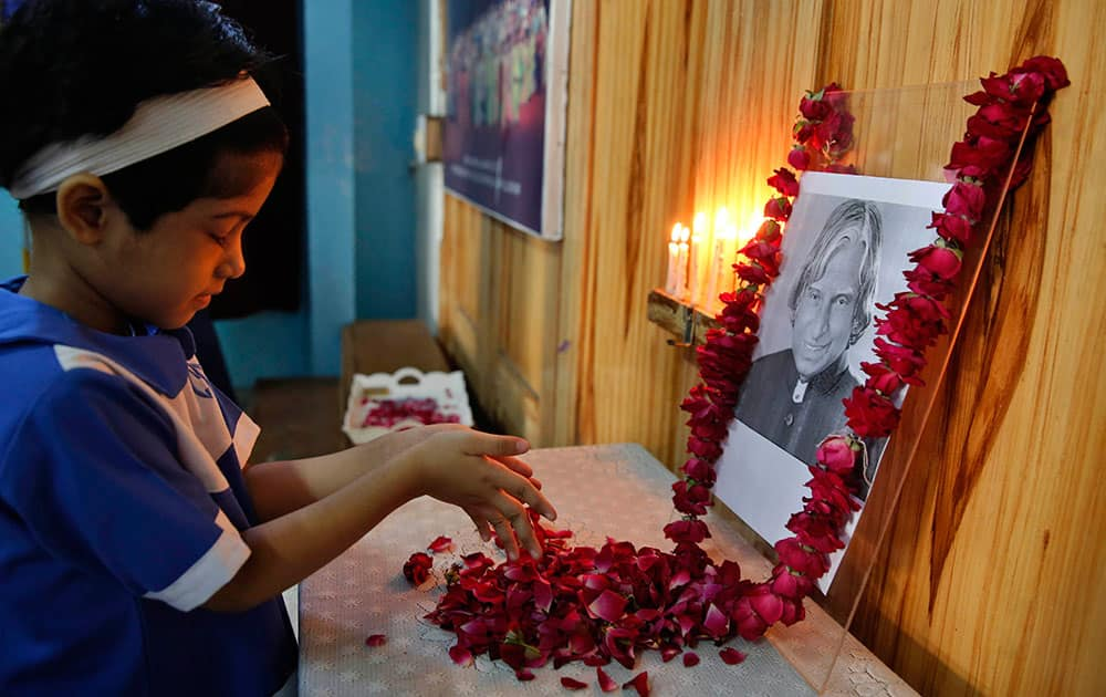 A student offers flowers to a portrait of former President A.P.J. Abdul Kalam at CMS School in Lucknow, India.