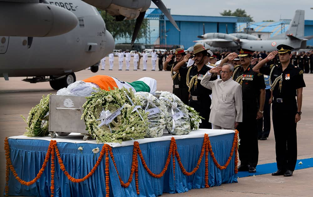 President Pranab Mukherjee, foreground, salutes the flag-draped casket of former President A.P.J. Abdul Kalam after his body arrived at the Palam airport in New Delhi, India.