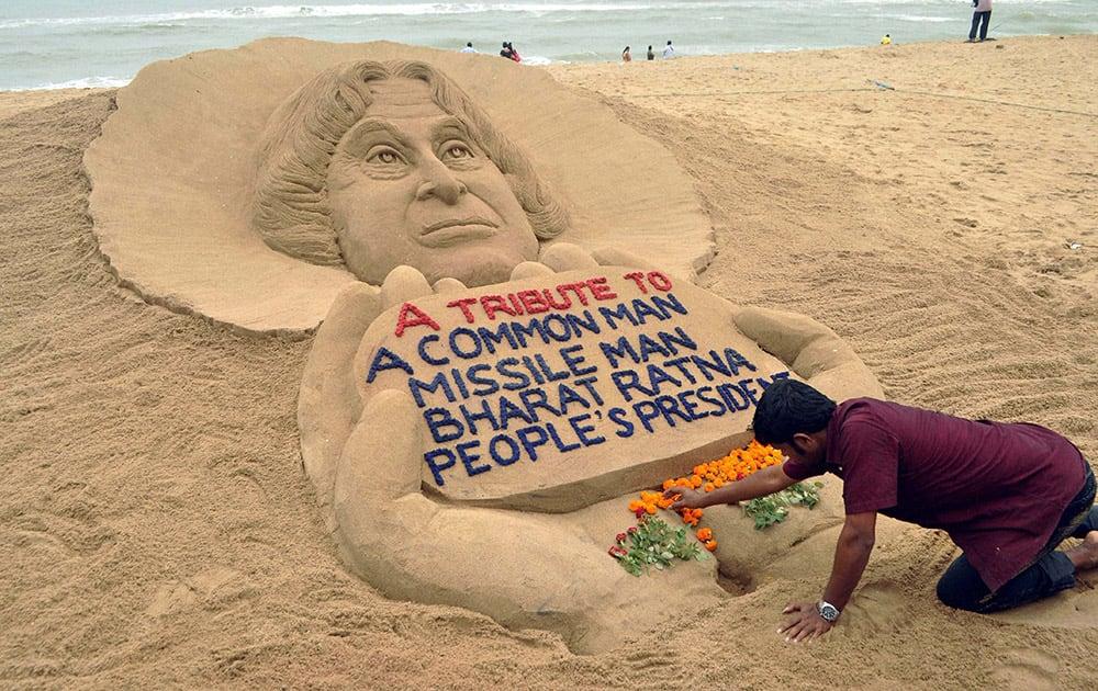Sand artist Sudarsan Pattnaik creates a sand sculpture to pay tribute to former President APJ Abdul Kalam, at Puri beach in Odisha.
