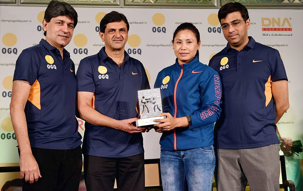 Former badminton player Prakash Padukone presents an award to boxer Sarita Devi as Viswanathan Anand and Geet Sethi look on during an event by Olympic Gold Quest in Bengaluru.