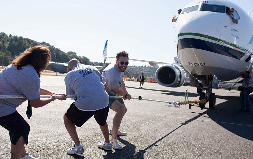 Joel McHale pulls the plane during the Alaska Airlines Plane Pull competition against Russell Wilson, benefiting Strong Against Cancer at The Museum of Flight in Seattle.