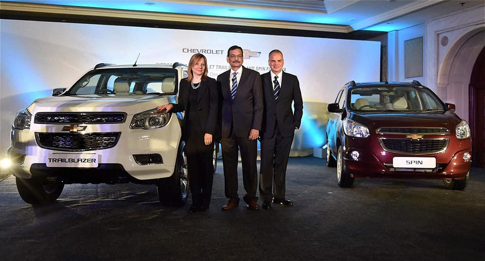 General Motors CEO Mary Barra with GM India President & MD Arvind Saxena and GM International President Stefan Jacoby pose for photographs with upcoming models of Chevrolet cars, in New Delhi.