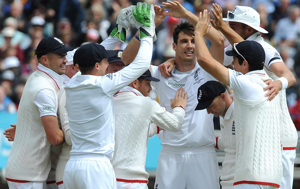 England's Steven Finn celebrates withteam-mates after bowling Australia's Michael Clarke for 10 runs during day one of the third Ashes Test cricket match, at Edgbaston, Birmingham, England.
