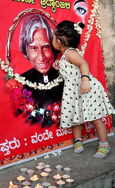 A child kisses former President APJ Abdul Kalams photo at Chikmagalur in Karnataka.