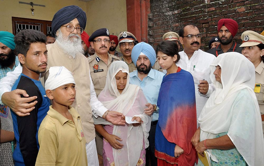 Punjab Chief Minister Parkash Singh Badal presents a cheque to the bereaved family members bereaved family members of Home Guard Jawan Sukhdev Singh at village Attepur in Pathankot.