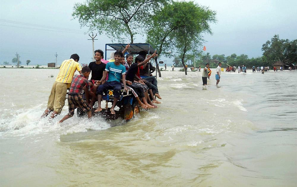 Locals wade through flood water at Karalaghat road in Burdwan district of West Bengal.