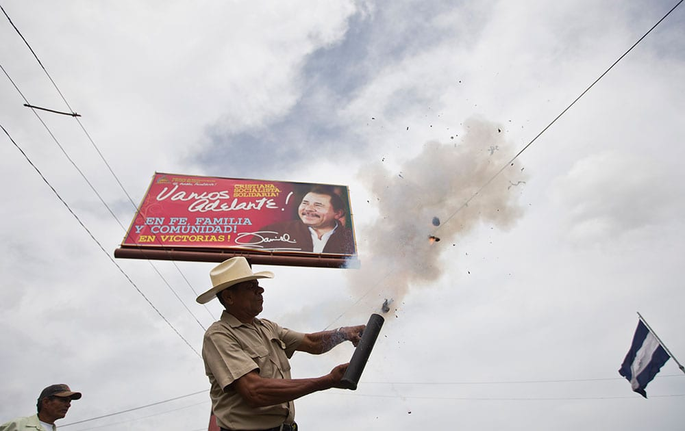 An anti-government protester fires a homemade mortar in front of a banner promoting Nicaragua's President Daniel Ortega, near the Supreme Electoral Council, during a demonstration demanding fair elections in Managua, Nicaragua.