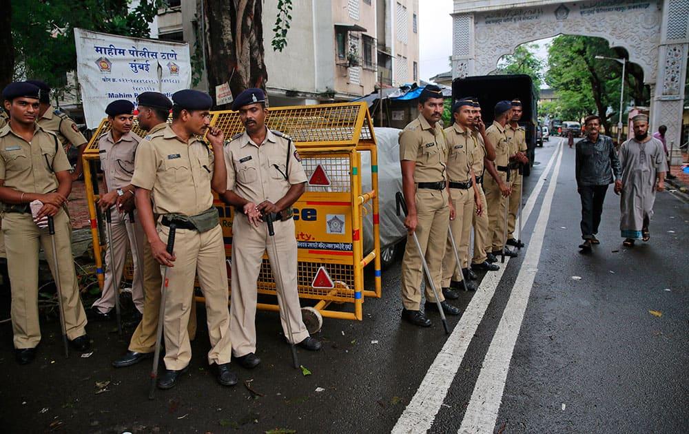 policemen stand guard in the neighborhood of Yakub Abdul Razak Memon's family residence in Mumbai.