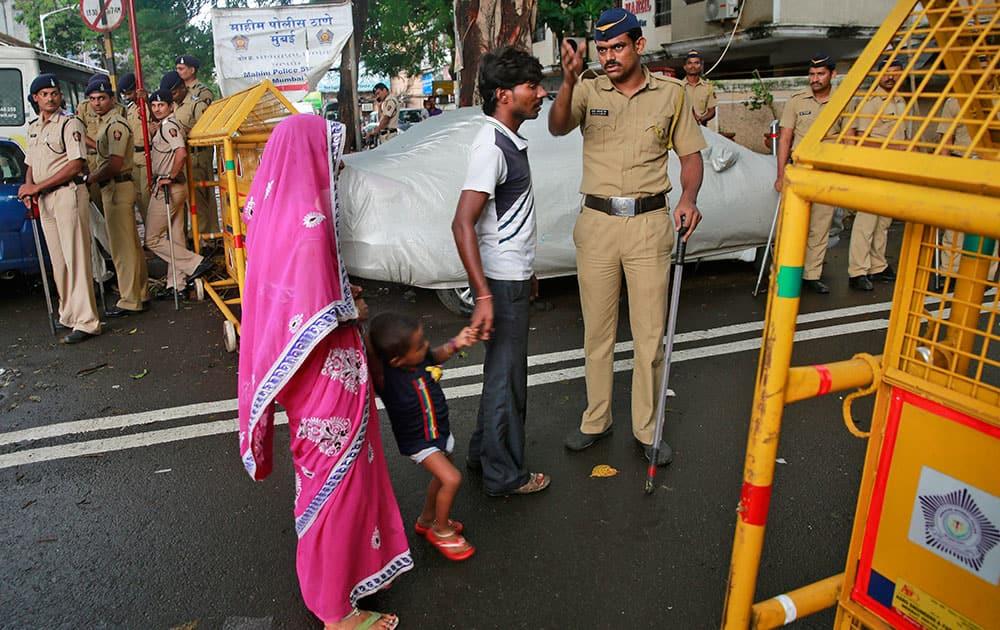 police officer stops a family at a barricade in the neighborhood of Yakub Abdul Razak Memon's family residence in Mumbai.