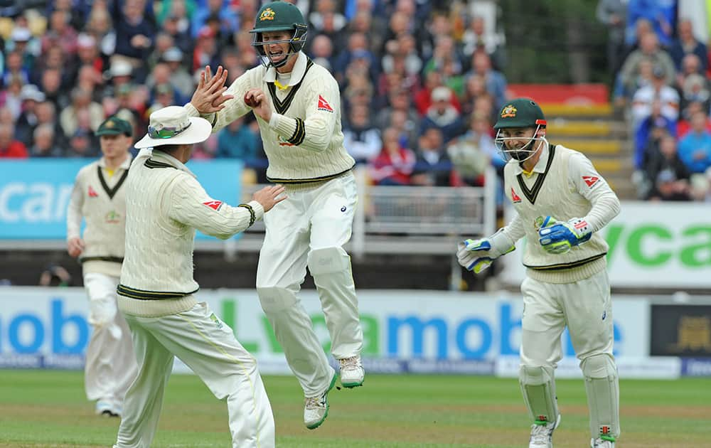 Australia's Adam Voges celebrates with Michael Clarke and Peter Nevill after he caught England's Alastair Cook bowled Australia's Nathan Lyon for 36 runs during day one of the third Ashes Test cricket match, at Edgbaston, Birmingham, England.