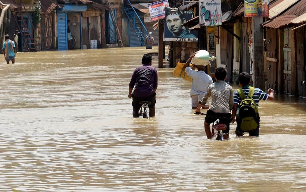 People wade through a flooded locality in West Midnapore district, West Bengal.