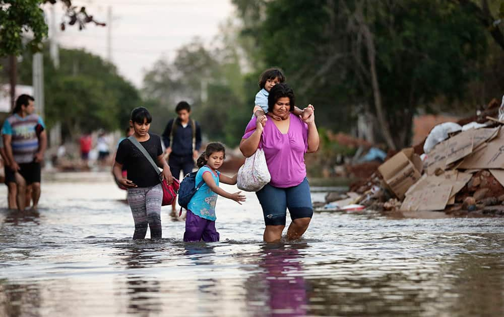 Victoria Barreto and her children wade through a flooded street to get to their school, in the Banado Norte neighborhood, in Asuncion, Paraguay.