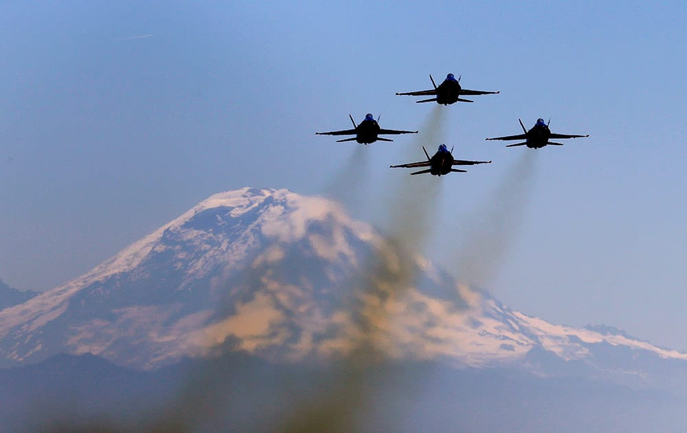 Members of the US Navy Blue Angels fly in formation as they take-off in view of Mount Rainier for an air show practice, from King County Airport in Seattle.