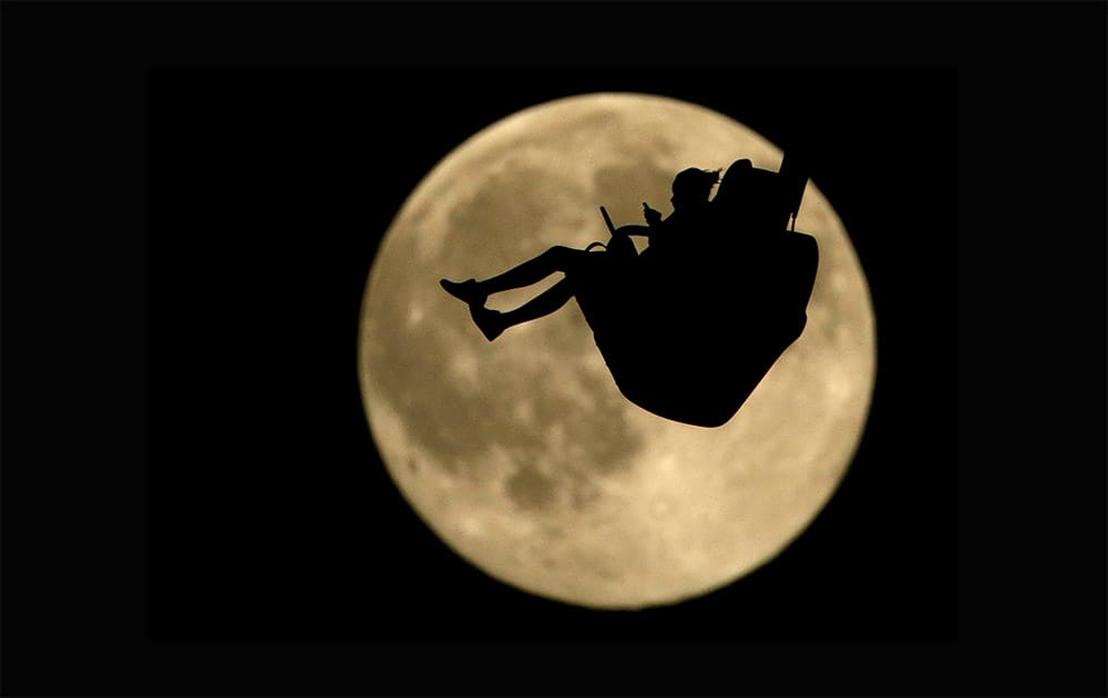 A girl is silhouetted against a rising full moon as she ride an attraction at Worlds of Fun amusement park, in Kansas City, Mo. When the full moon appears at 6:43 a.m. EDT (1043 GMT) in the US Friday, it will become the second full moon of July. Geoff Chester of the US Naval Observatory said the traditional definition of a blue moon is two full moons in a month.