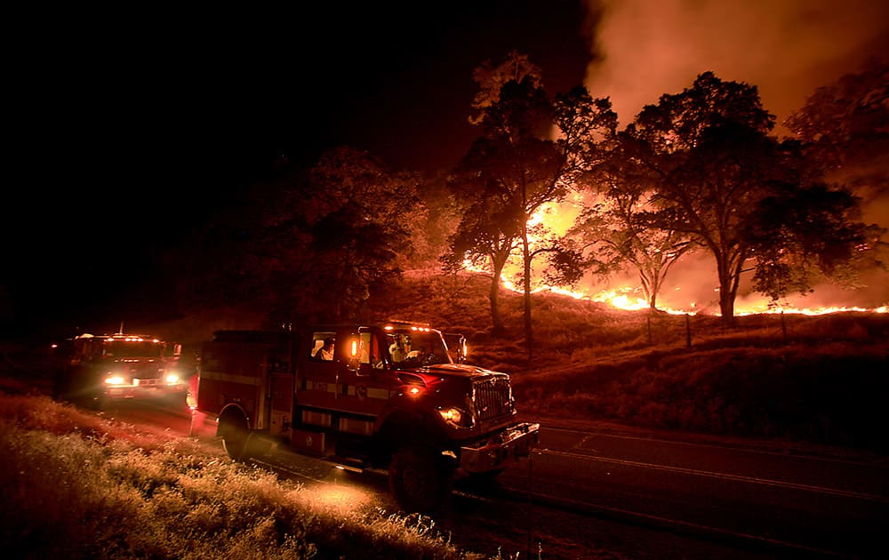 Cal Fire crews from Napa's Greenwood Ranch Station monitor a fire, near Lower Lake, Calif.