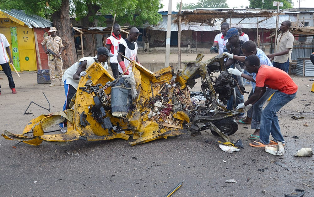 People inspect a damaged tricycle at the site of a bomb explosion in Maiduguri, Nigeria. A woman suicide bomber killed many people at a crowded market early Friday in a blast that thundered across the northeastern Nigerian city of Maiduguri, witnesses said.