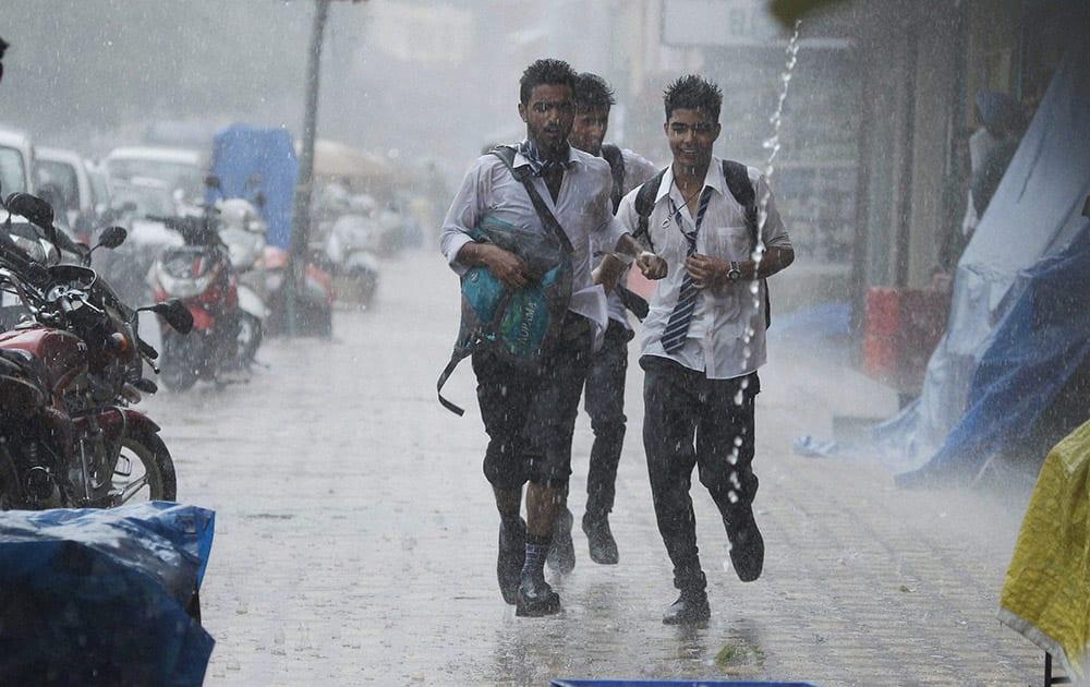 School students run for shelter as it rains in Srinagar.
