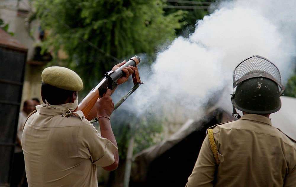 A policeman fires tear gas shells to disperse a group of protesters demonstrating during second day of Jammu bandh over AIIMS issue.