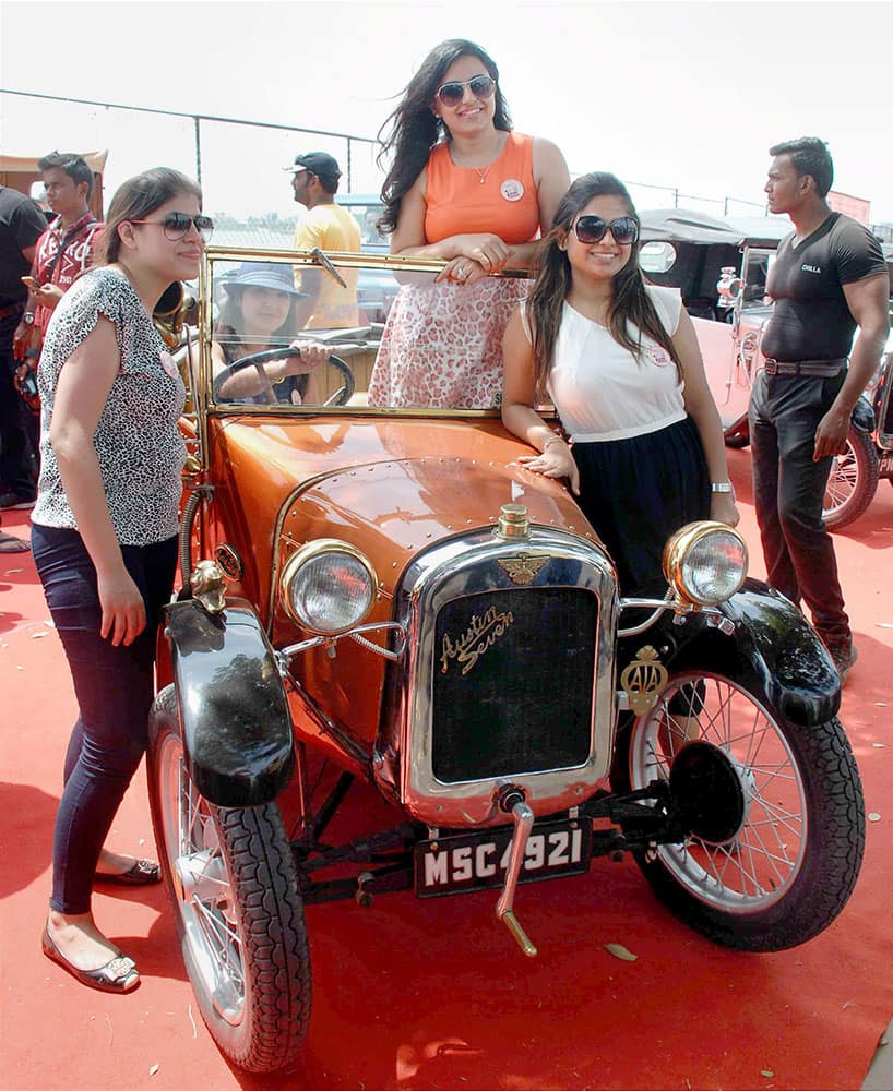 Women pose with a Vintage car at the Women Driven Vintage Car Rally as a part of the Road Safety awareness in Hyderabad.