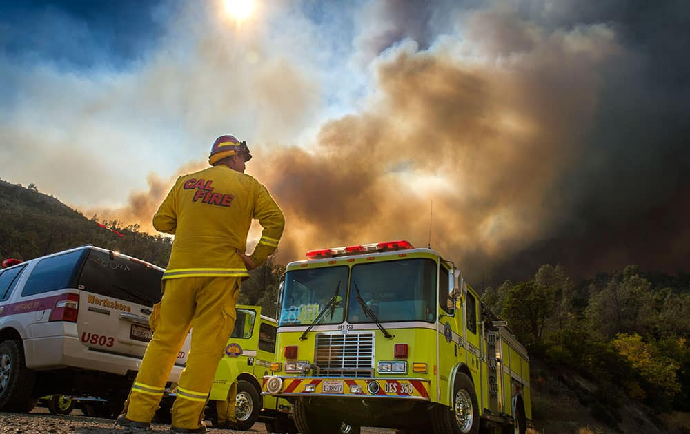 Dave Miinch, fire captain with South Lake County, watches a fire burn on the north side of U.S. Highway 20, in Yolo County, Calif.