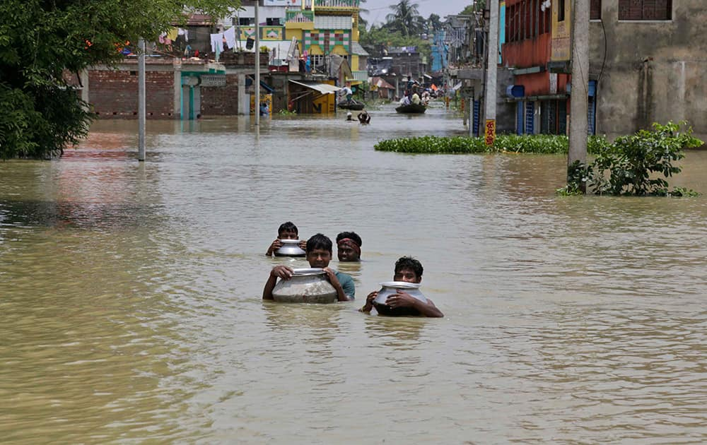 Villagers wade through flood waters with the help of empty utensils as they try to reach their house at Khanakul, about 100 kilometers (62 miles) west of Kolkata.