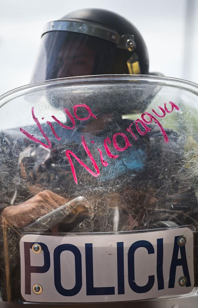 A riot police officer holds his shield after it was scribbled on with lipstick with the message in Spanish