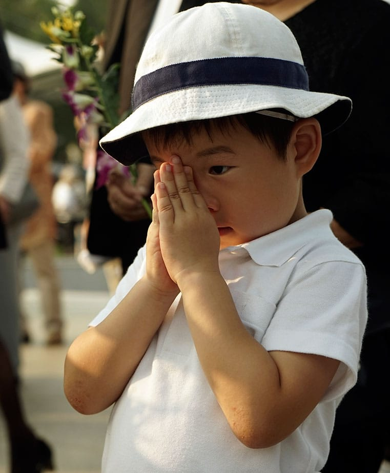 A boy prays for the atomic bomb victims in front of the cenotaph at the Hiroshima Peace Memorial Park in Hiroshima, western Japan.