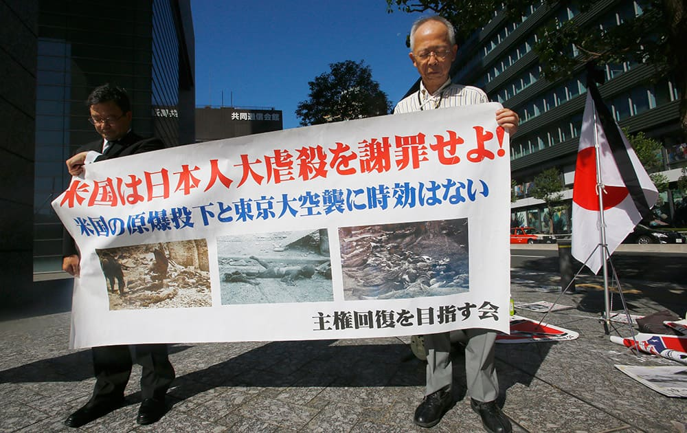 Members of a rightist group offer silent prayers for the victims of the atomic bombing with anti-US banner near the US Embassy in Tokyo. Japan marked the 70th anniversary of the atomic bombing of Hiroshima.
