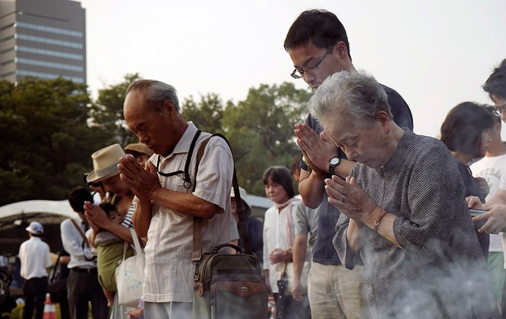 Buddhist monks pray for the atomic bomb victims in front of the cenotaph at the Hiroshima Peace Memorial Park in Hiroshima, western Japan.