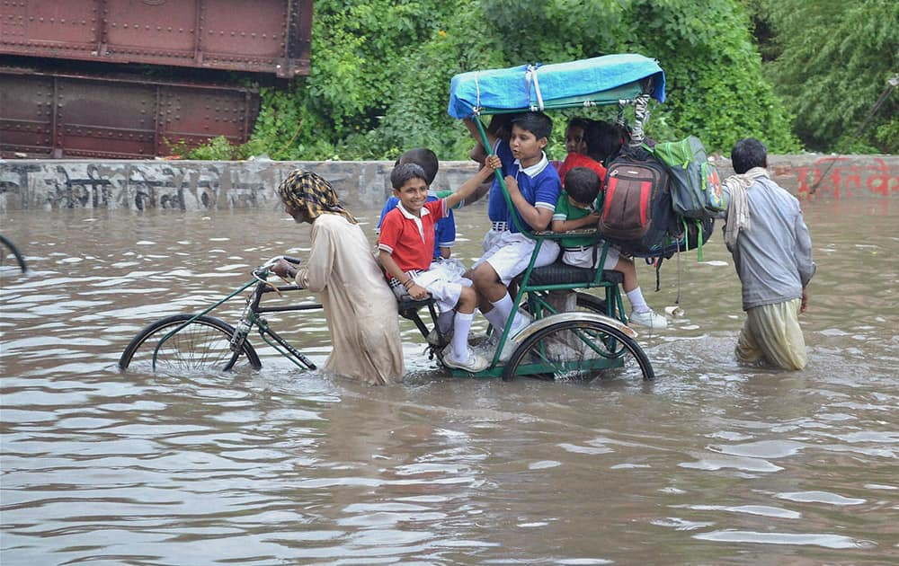 School children move through a flooded street after heavy rainfall in Mathura.
