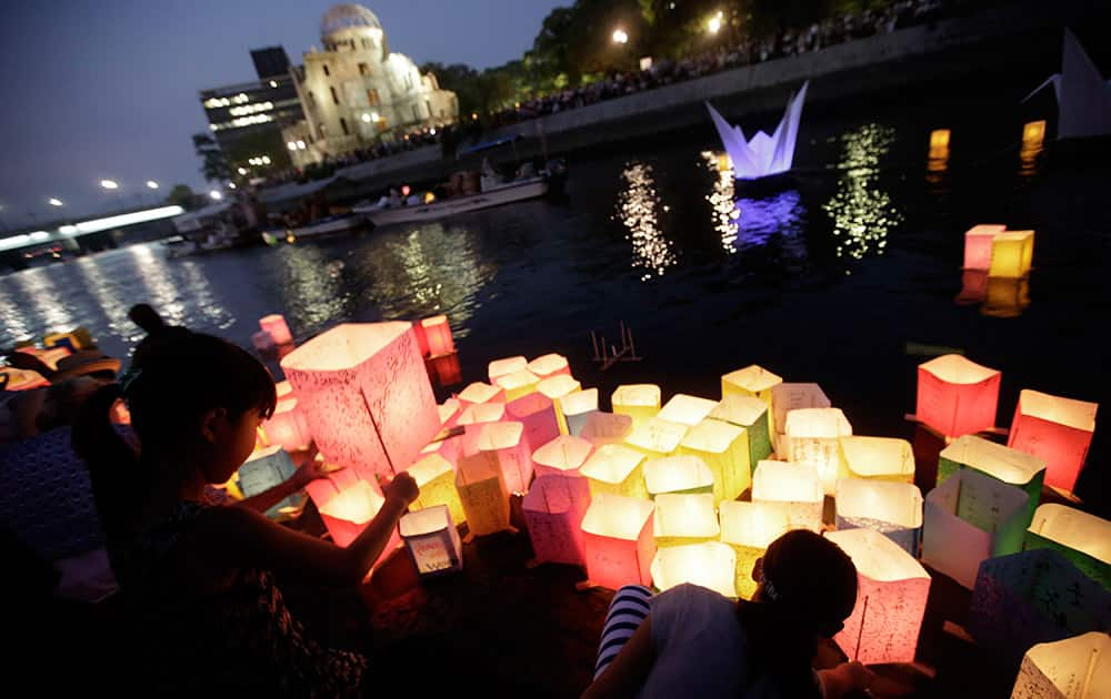 Children offer prayers as after releasing paper lanterns to the Motoyasu River where hundreds of thousands of atomic bombing victims died with the backdrop of the Atomic Bomb Dome in Hiroshima, western Japan. Japan marked the 70th anniversary Thursday of the atomic bombing of Hiroshima.