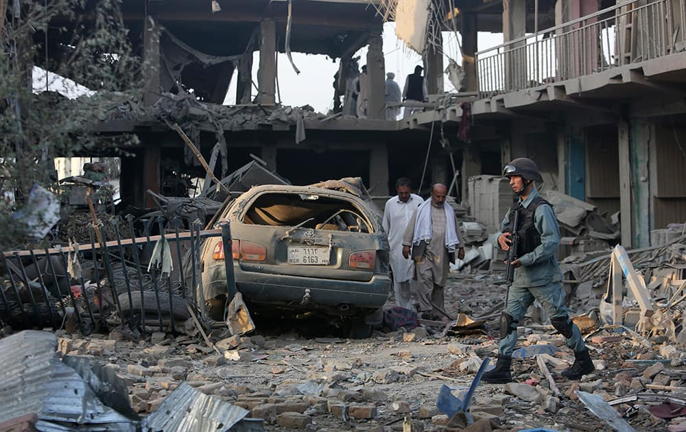 An Afghan police officer, walks at the site of a car bomb attack in Kabul, Afghanistan. A bomb hidden in a truck exploded in the center of the Afghan capital. Police chief Abdul Rahman Rahimi said the pre-dawn blast was near a Defense Ministry compound, but that all of the victims were civilians, including women and children.