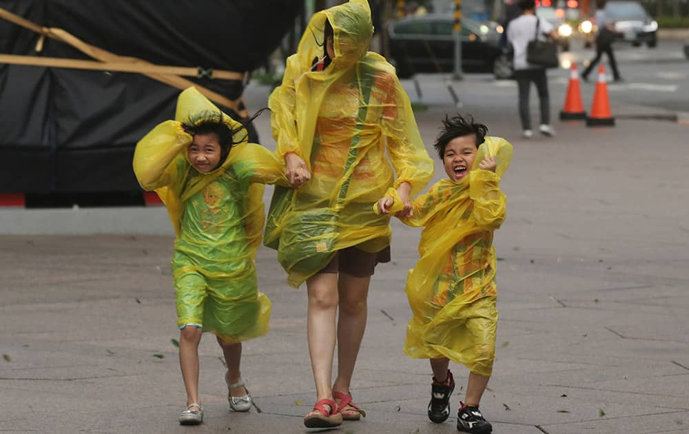 A woman and children brave the strong winds from Typhoon Soudelor in Taipei, Taiwan.