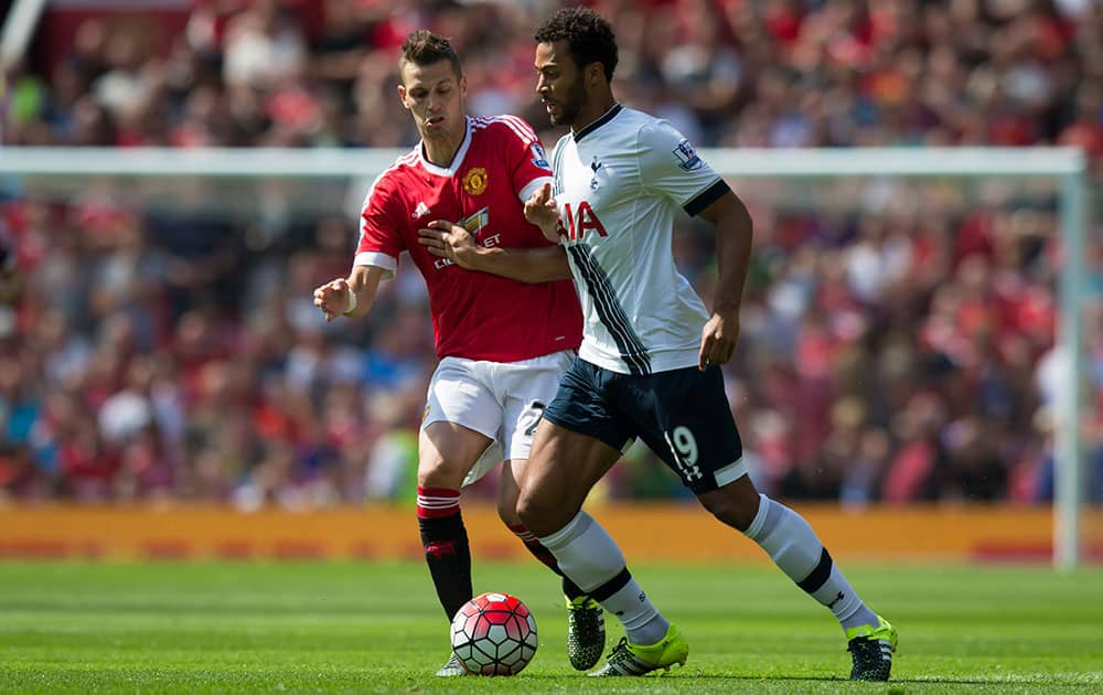 Manchester United's Morgan Schneiderlin, left, fights for the ball against Tottenham's Mousa Dembele during the English Premier League soccer match between Manchester United and Tottenham at Old Trafford Stadium, Manchester, England.