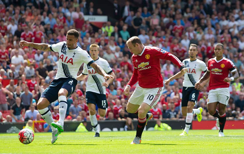 Tottenham's Kyle Walker, left, scores an own goal as he tries to clear the ball away from Manchester United's Wayne Rooney during the English Premier League soccer match between Manchester United and Tottenham at Old Trafford Stadium, Manchester, England.