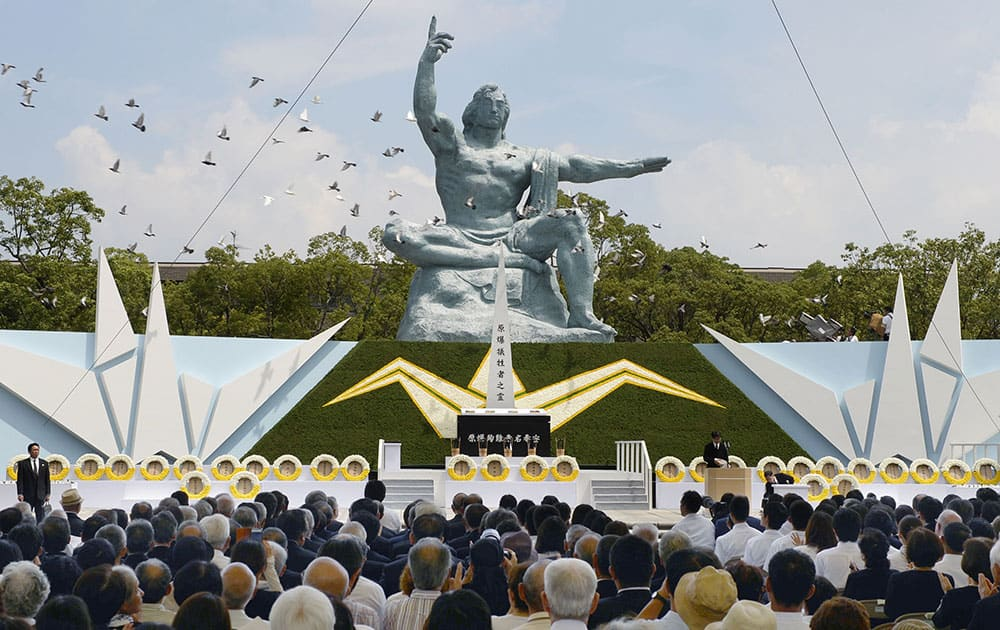 Doves fly over the Statue of Peace during a ceremony at Nagasaki Peace Park in Nagasaki.