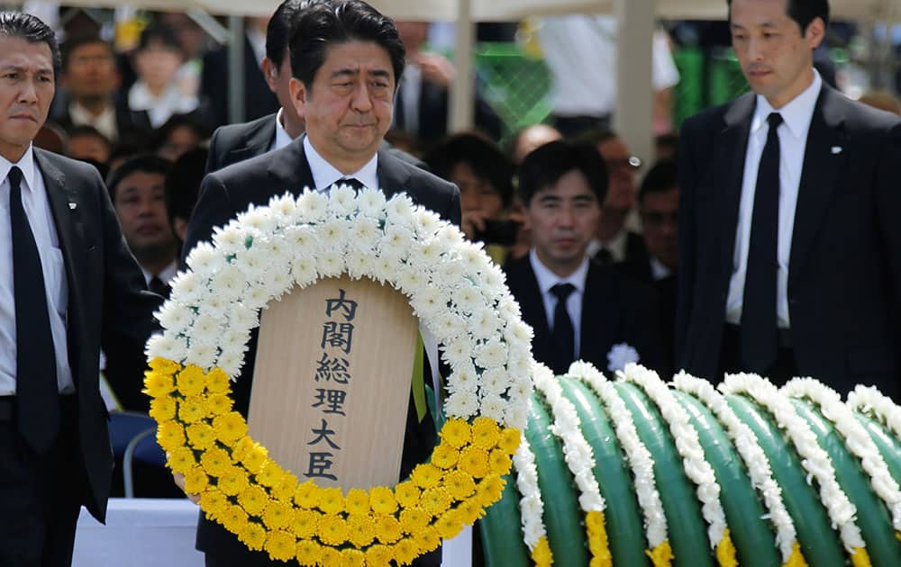 Japanese Prime Minister Shinzo Abe holds a wreath during a ceremony to mark the 70th anniversary of the Nagasaki atomic bombing in Nagasaki.