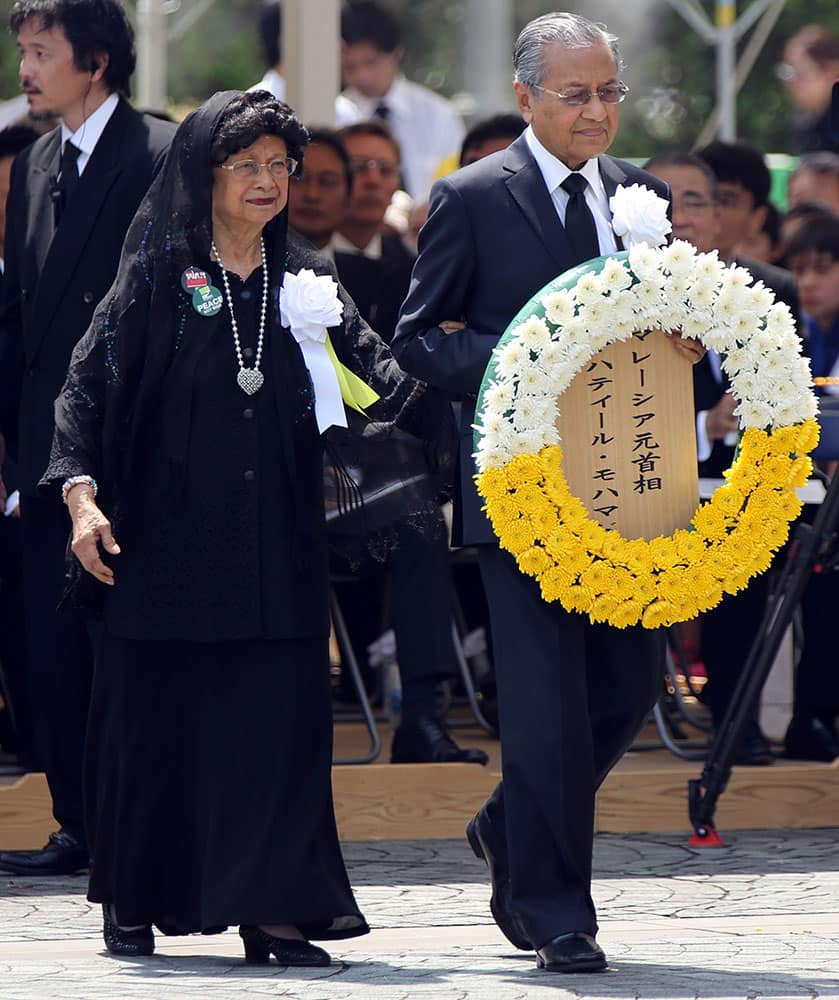 FORMER MALAYSIAN PRIME MINISTER MAHATHIR MOHAMAD, RIGHT, AND HIS WIFE SITI HASMAH, LEFT, BRING A WREATH DURING A CEREMONY TO MARK THE 70TH ANNIVERSARY OF THE ATOMIC BOMBING IN NAGASAKI.