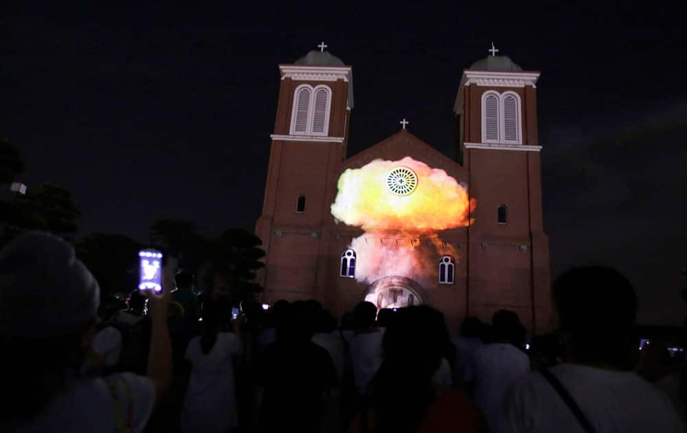 Visitors watch a computer-generated video of a mushroom cloud of 1945 atomic bomb dropped over the city projected on Urakami Cathedral on the eve the 70th anniversary of the Nagasaki Atomic Bombing in Nagasaki