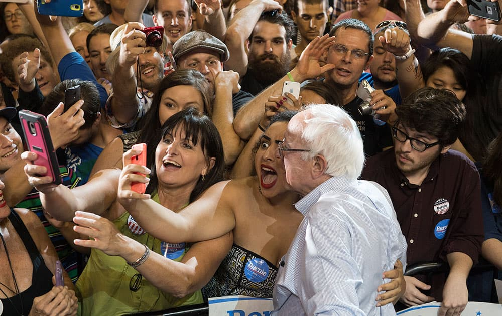 Naomi Scott, center, of McMinnville, Ore., takes a picture with Democratic presidential candidate Sen. Bernie Sanders, I-Vt., at a rally, at the Moda Center in Portland, Ore.