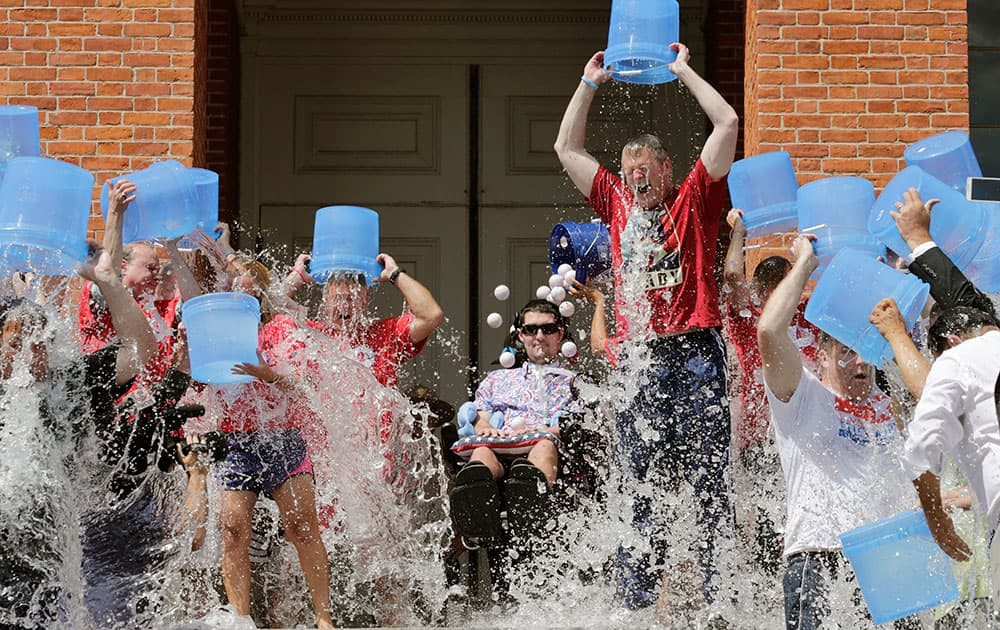 Massachusetts Gov. Charlie Baker, right center, and Lt. Gov. Karyn Polito, third from left, participate in the Ice Bucket Challenge with its inspiration Pete Frates, seated in center, to raise money for ALS research at the Statehouse in Boston.