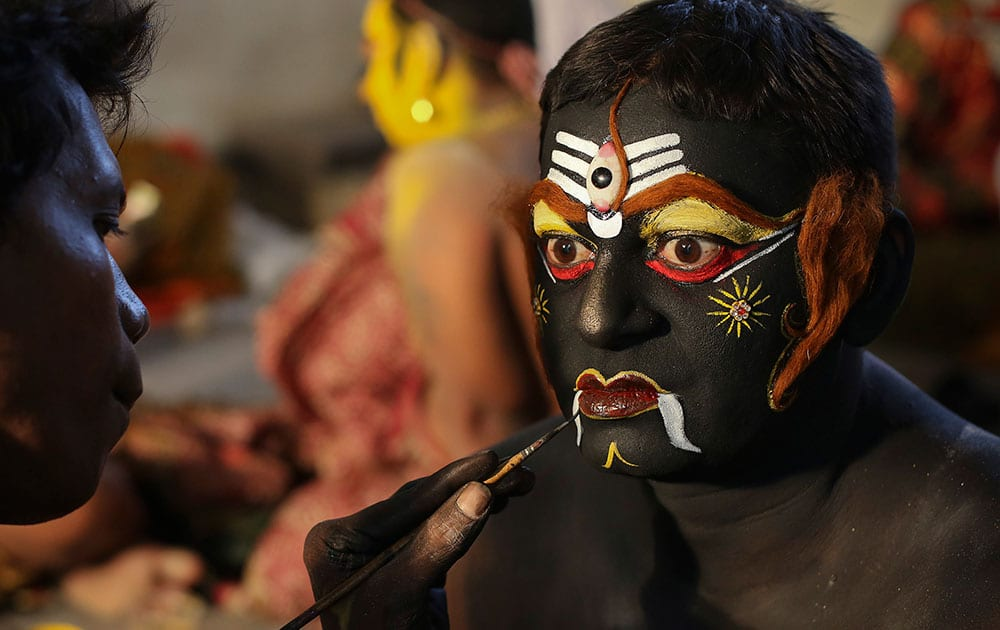 An Indian artist gets make up before a performance during a procession as part of