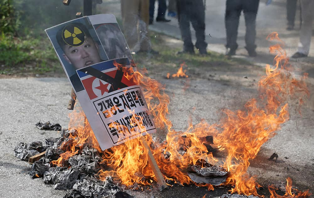 Members of South Korean conservative group burn a picture of North Korean leader Kim Jong Un and North Korea's flag during a rally denouncing the North Korea at the Imjingak Pavilion near the border village of Panmunjom, which has separated the two Koreas since the Korean War, in Paju, north of Seoul, South Korea.