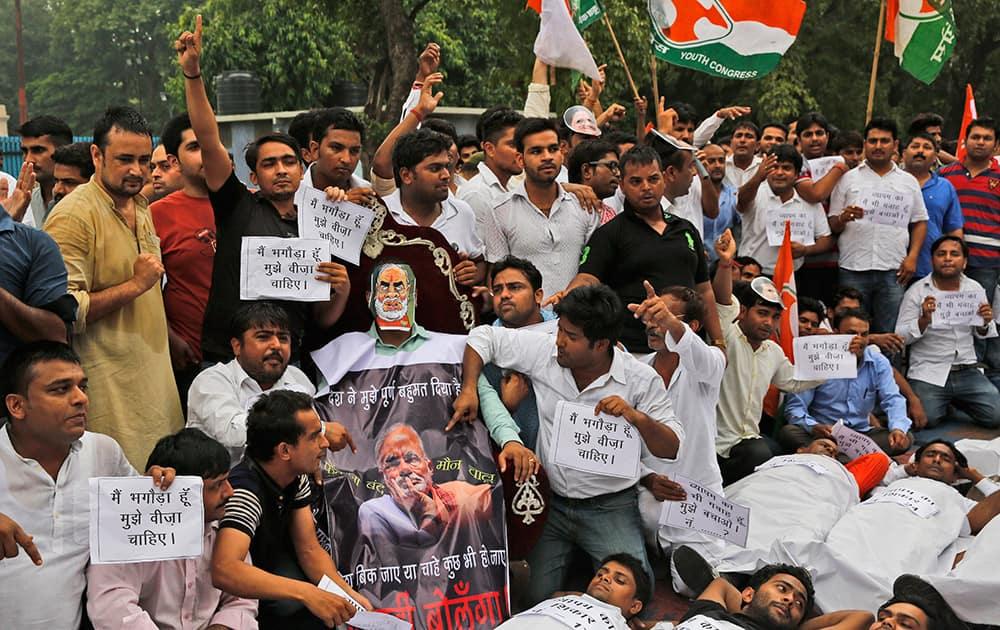 Congress party's youth wing activists shout slogans demanding the resignation of three key ruling party leaders accused of abusing their authority and financial irregularities during a protest near the Indian Parliament in New Delhi.