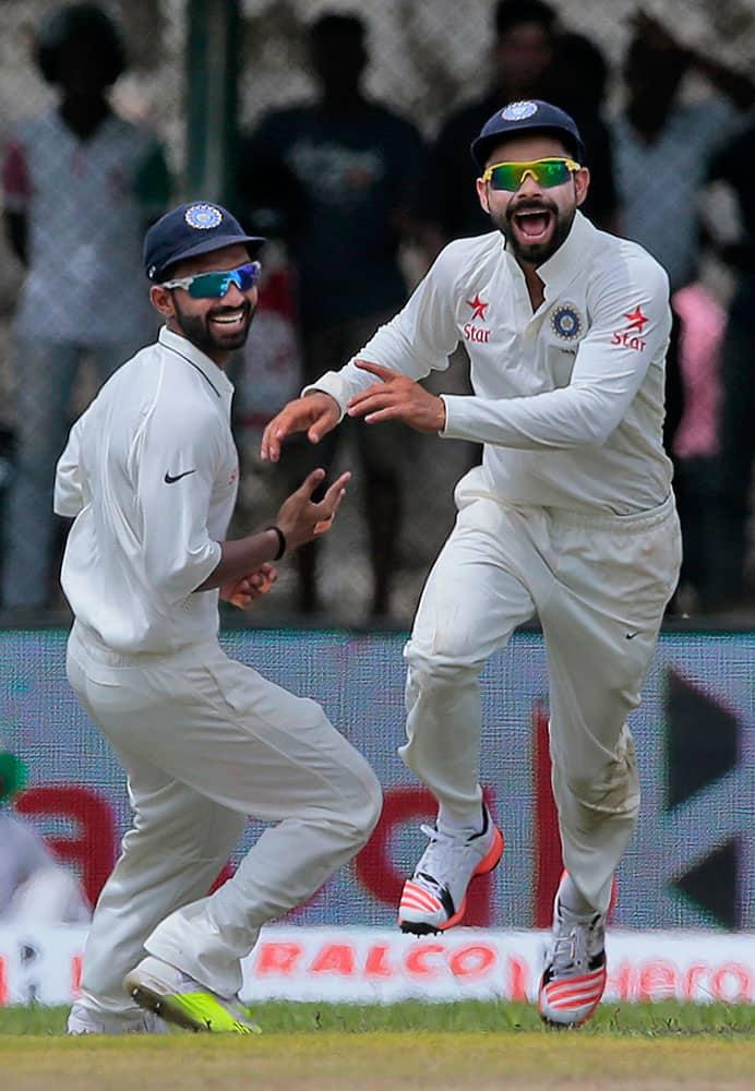 India's captain Virat Kohli, right, celebrates with teammate Ajinkya Rahane the dismissal of Sri Lanka's Kaushal Silva during their first cricket test match in Galle, Sri Lanka.