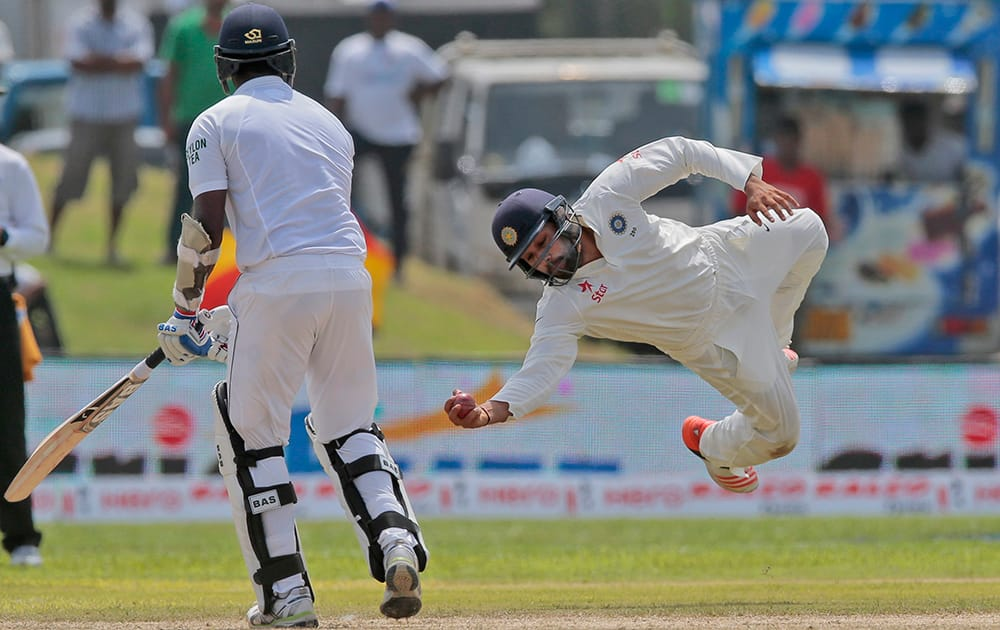 Rohit Sharma successfully completes a catch to dismiss Sri Lanka's Angelo Mathews during the first cricket test match between India and Sri Lanka in Galle.