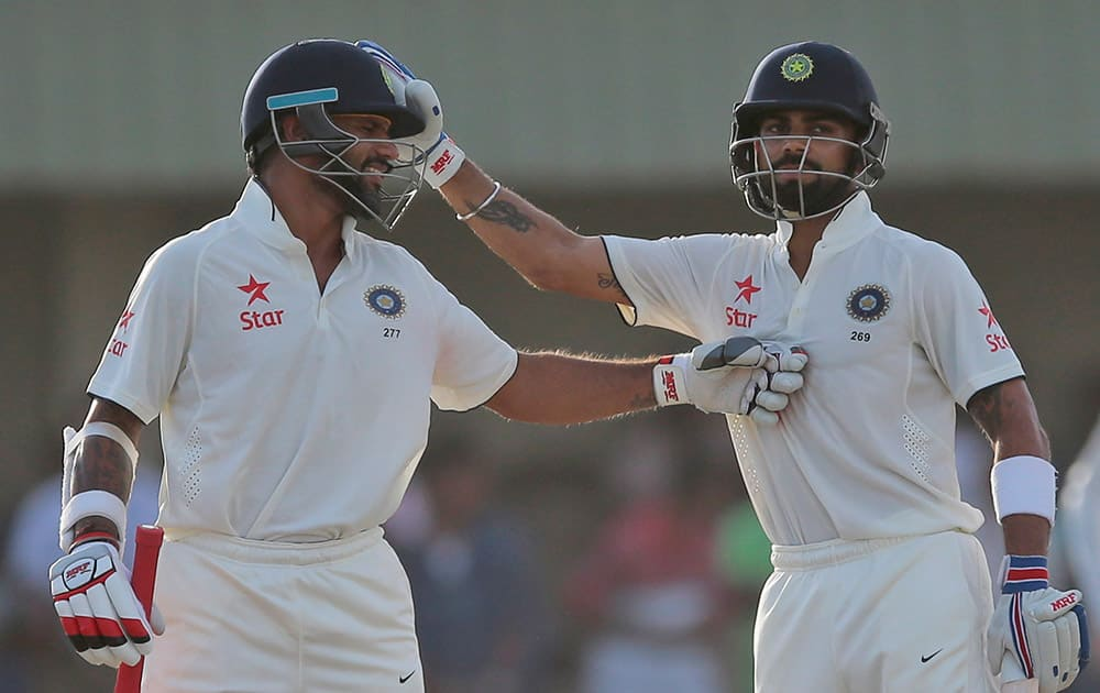 Virat Kohli and Shikar Dhawan cheer each other as they complete their hundred runs partnership during the first cricket test match between India and Sri Lanka in Galle, Sri Lanka.