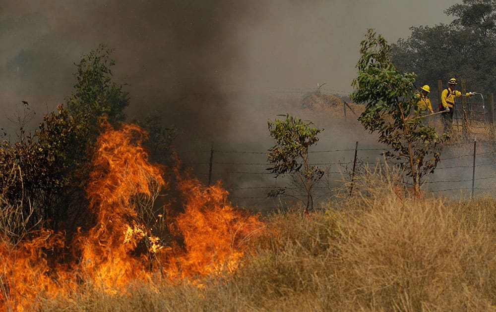 A fire crew works a back fire along Morgan Valley Road near Lower Lake, Calif.
