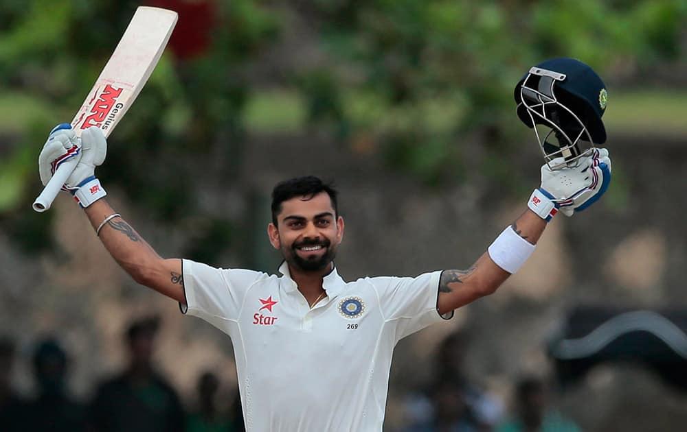 Virat Kohli celebrates scoring a century during the second day of their first test cricket match against Sri Lanka in Galle, Sri Lanka.